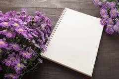 Las flores y el cuaderno púrpuras del cortador están en el fondo de madera Foto de archivo