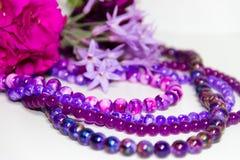 Las flores y los accesorios femeninos y románticos de las perlas en el año ultravioleta entonan Fotografía de archivo libre de regalías