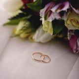 Las flores y los anillos de la boda se cierran para arriba imagenes de archivo