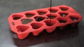 Las formas bajo la forma de corazones se vierten con el chocolate derretido metrajes
