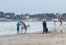 Las fotografías del fotógrafo como instructor entrenan a un hombre joven para montar un caballo en la costa mediterránea cerca imagen de archivo libre de regalías