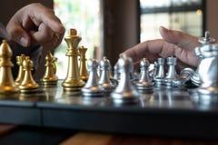 Las fotos del primer de las manos del jaque mate en un tablero de ajedrez durante un juego de ajedrez el concepto de estrategia d fotografía de archivo