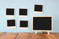 Las fotos inmediatas en blanco cuelgan sobre fondo texturizado de madera al lado de la pizarra en blanco Foto de archivo