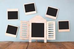 Las fotos inmediatas en blanco cuelgan sobre fondo texturizado de madera al lado de la pizarra en blanco Foto de archivo libre de regalías