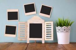 Las fotos inmediatas en blanco cuelgan sobre fondo texturizado de madera al lado de la pizarra y de la maceta en blanco Fotografía de archivo libre de regalías