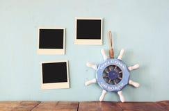 Las fotos inmediatas en blanco cuelgan sobre fondo texturizado de madera al lado del volante del vintage con la recepción de la f Fotografía de archivo