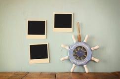 Las fotos inmediatas en blanco cuelgan sobre fondo texturizado de madera al lado del volante del vintage con la recepción de la f Imagenes de archivo