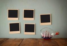 Las fotos inmediatas vacías en blanco cuelgan sobre fondo texturizado de madera al lado del barco decorativo en la botella imagen Foto de archivo