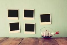 Las fotos inmediatas vacías en blanco cuelgan sobre fondo texturizado de madera al lado del barco decorativo en la botella imagen Foto de archivo libre de regalías