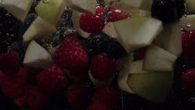Las frambuesas, los arándanos, las zarzamoras y los pedazos de Apple caen en el agua en un fondo negro Cámara lenta Orgánico almacen de video