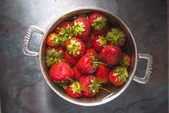 Las fresas en una lata ruedan en el centro de la tabla Fotos de archivo libres de regalías