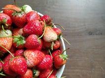 Las fresas frescas están en el cuenco blanco en la tabla de madera imagen de archivo