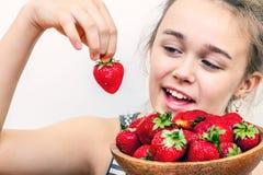 Las fresas hermosas frescas en cuenco de madera en las muchachas dan fotografía de archivo libre de regalías