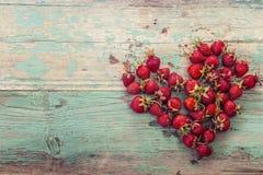 Las fresas maduras en un corazón forman en backgrou de madera envejecido verde Fotografía de archivo libre de regalías