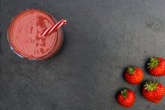 Las fresas rojas del smoothie beben el fondo oscuro Fotografía de archivo