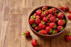 Las fresas rojas frescas en una arcilla marrón ruedan en la tabla de madera Foto de archivo libre de regalías