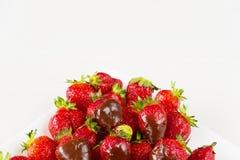 Las fresas sumergieron en chocolate delicioso en el plato blanco aislado en el fondo blanco Ciérrese encima de la visión Imagenes de archivo