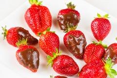 Las fresas sumergieron en chocolate delicioso en el plato blanco aislado en el fondo blanco Ciérrese encima de la visión Foto de archivo