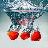 Las fresas vibrantes rojas en el agua salpican en fondo negro foto de archivo libre de regalías