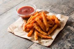 Las fritadas y la salsa de tomate de la patata dulce sauce en la madera Fotografía de archivo