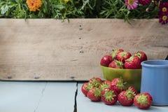 Las frutas dispersadas de la fresa en cuenco verde Foto de archivo