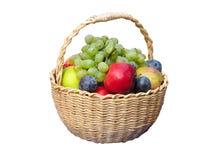 Las frutas frescas arreglaron en una cesta de mimbre aislada en blanco Imagen de archivo