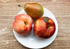 Las frutas frescas están mintiendo en un fondo marrón en una placa blanca imagen de archivo