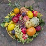Las frutas mezcladas en una cesta de la rota, con la hiedra se van Imagenes de archivo