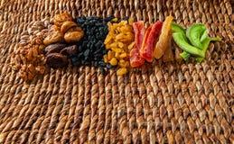 Las frutas secadas de las frutas, nuts y escarchadas extendieron por una superficie de mimbre foto de archivo libre de regalías