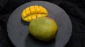 Las frutas tropicales orgánicas, cierre para arriba resbalan los mangos en la placa negra metrajes