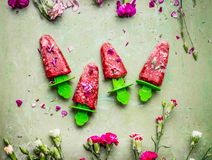 Las frutas y el helado o los polos hechos en casa rosados de las bayas en el fondo rústico de la tabla verde del trullo, adornado fotos de archivo