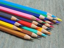 Las fuentes de escuela colorean virutas de los lápices en la tabla de madera Foto de archivo