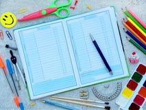 Las fuentes de escuela y el libro de día abierto con la pluma rematan la frontera Fotografía de archivo