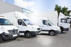 Las furgonetas de entrega comerciales parquean en el aparcamiento del transporte de transportar servicio de envío del portador fotografía de archivo