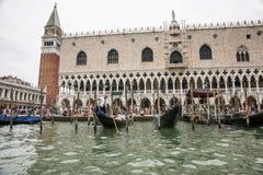 Las góndolas y el gondolero con los turistas acercan al palacio de los duxes en summe Fotos de archivo libres de regalías