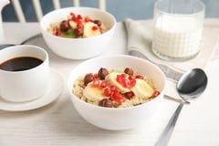 Las gachas de avena de la quinoa con las semillas de las avellanas, del kiwi, del plátano y de la granada sirvieron para el desay foto de archivo