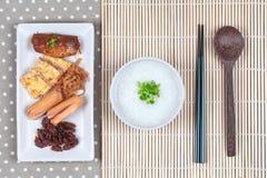 Las gachas del arroz sirvieron con la salchicha, las almejas, el rábano, la tortilla y el mackere Imagenes de archivo