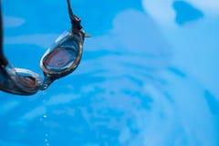 Las gafas de la natación del foco selectivo con agua caen en la natación Foto de archivo