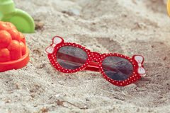 Las gafas de sol de los niños mienten en una playa en la arena Fotos de archivo libres de regalías