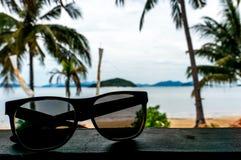 Las gafas de sol de un turista en el restaurante de la playa Imagenes de archivo