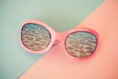 Las gafas de sol del rosa de la moda que reflejan el mar en un fondo rosado y azul Fotos de archivo libres de regalías