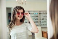 Las gafas de sol elegantes hacen mirada de la persona de moda Retrato de la muchacha europea joven apuesta sonriente en tienda de Fotos de archivo