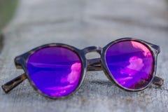 Las gafas de sol mienten en una tabla de madera, reflejan el cielo y la nube Foto de archivo libre de regalías