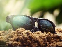 Las gafas de sol se cubren con gotas de lluvia están en Imagen de archivo libre de regalías