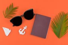 Las gafas de sol y el pasaporte adornan con las hojas del helecho y velero y ancla minúsculos fotografía de archivo libre de regalías