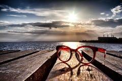 Las gafas hermosas en el puente de madera extendieron en el mar cerca Imagen de archivo