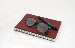 Las gafas y la pluma en el cuaderno rojo oscuro y el anillo negro de la espina dorsal reservan fotos de archivo