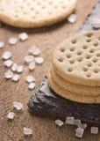 Las galletas apilan juntas en la piedra negra, azúcar grueso en b de madera Foto de archivo libre de regalías