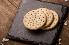 Las galletas apilan juntas en la piedra negra, azúcar grueso en b de madera Fotografía de archivo