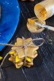 Las galletas atadas con un oro del piñón de la cuerda teñen, asperjando, creatividad, estrella de la Navidad del arte Foto de archivo